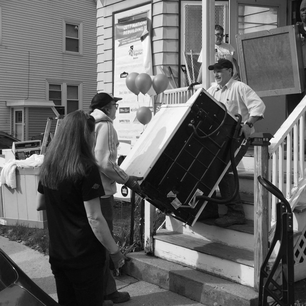 Volunteers carrying heavy appliances at the Claremont Street Repair